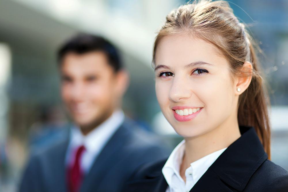 Photo d'une hôtesse d'accueil en premier plan et d'un hôte d'accueil en second plan flouté